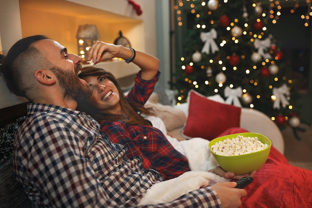 Couple at Christmas eve enjoy with popcorn while watching tv